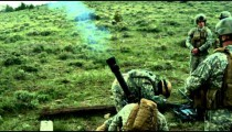 Slow motion shot of soldiers ducking while firing a mortar at range.