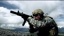 Close up of a soldier with sub-machine gun down, aiming, firing, and lowering weapon.