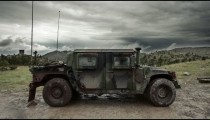 Humvee sitting in mud with storm clouds in the sky.