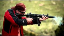 Man in baseball cap and red jacket shooting an MP5