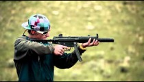 Man in baseball cap and blue jacket shooting an MP5