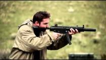 Man in a tan jacket shoots an MP5