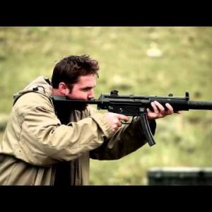 Man in a tan jacket shoots an MP5