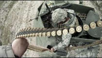 Soldier shoots humvee machine gun while tank is in motion