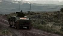 Humvee on a dirt road amid training explosives.