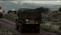 Two Humvees on a dirt road, training explosives create smoke and explode.