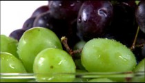 Tilt up shot of nectarines and grapes rotating on a white screen.