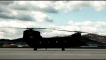 Time-lapse footage of a Chinook helicopter at an airfield.