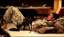 Soldier lying on the ground, talking on a cell phone.