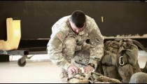 Soldier preparing his gear in a hangar.