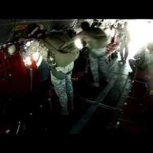 Paratroopers looking out the windows of a CH-47 Chinook helicopter.