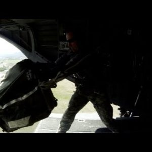 Crew member on a CH-47 Chinook helicopter adjusts something.