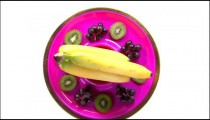 Assortment of fruit on a rotating purple plate.
