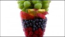 Zoom out shot of an assortment of fruit in a vase.