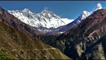 Time-lapse of the tip of Everest and surrounding peaks and trekkers on a foreground trail.