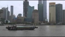 Barges travel down Huangpu River against a background of skyscrapers