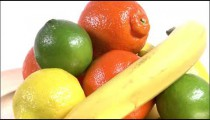 Varied fruits rotating on a white screen.