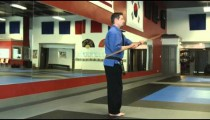 Man in a karate studio practing bow staff weapon moves