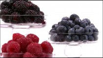 Three glasses of berries on a white screen.