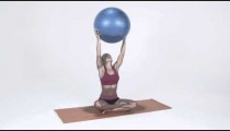 Young woman sitting on a yoga mat lifts a yoga ball above her head