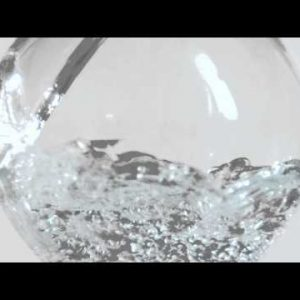 Water curls off the curved side of a fish bowl shaped glass in slow motion as container fills