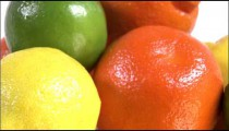 Close shot of citrus fruits rotating on a white screen.