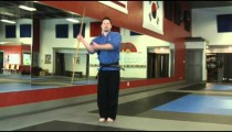 Man in a karate studio practicing bow staff weapon moves