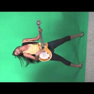 Full body shot of a girl dancing and strumming electric guitar