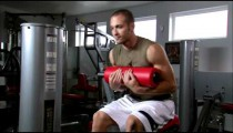 Man doing sitting curls in a gym weight room.