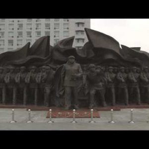"""Shot of a statue of soldiers labeled """"For Peace"""" in China."""
