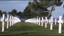 Looking down a row of white crosses gravemarkers in the American cemetery in Norman France.