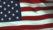 Panning close up of the American flag rolling in the wind.