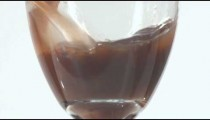 Close up of elongated tulip shaped wine glass filled with a brown liquid in slow motion