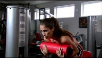 Woman doing sitting curls in a gym weight room.