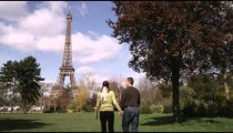 A couple walking hand in hand at a park with the Eiffel Tower in the background.