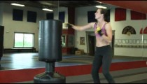 female doing punch kick combos on a punching bag