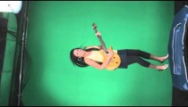 Girl holding an electric guitar and jumping on a trampoline