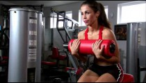 Woman doing sitting curls on an exercise machine.