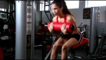 Woman doing curls on an exercise machine.