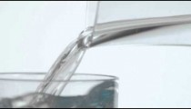 Extreme close up of water pouring from one glass container into another