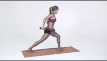Young woman does arm exercises standing on a yoga mat in workout attire