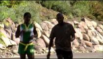 Couple jogging down a road.
