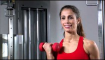 Woman doing arm curls with a pair of dumbbells.