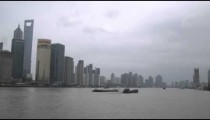 Barges turn with Huangpu River against a background of skyscrapers