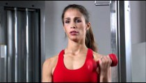 Woman doing arm curls with a pair of dumbbells in a weight room.
