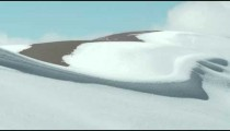 Pan of crest of snowy hills