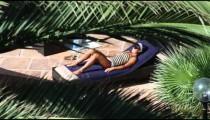 Sunbathing woman at a resort pool side.