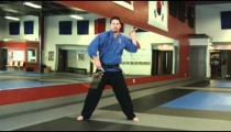 Man in a karate studio practicing nunchuch weapon moves