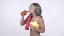 Blonde female drinks energy drink in work out attire