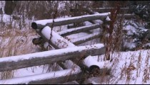 Rural stacked-wood fence in a snow-covered field